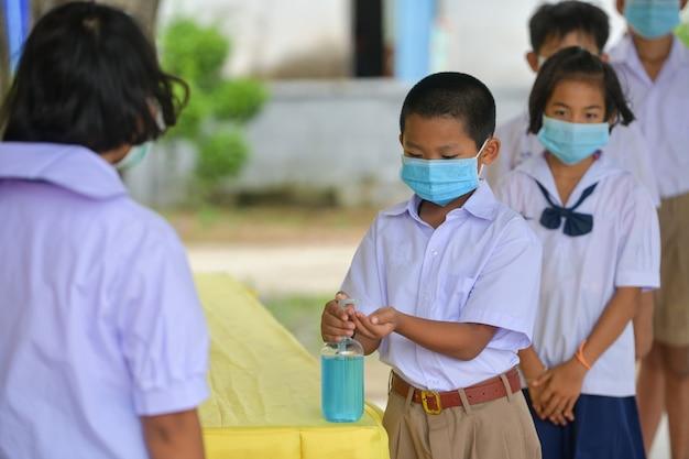 Lavarsi le mani con gel igienizzante per la prevenzione della malattia da coronavirus in classe.