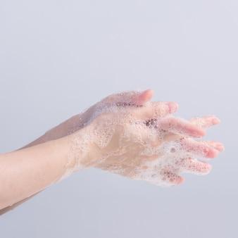 Lavarsi le mani. giovane donna asiatica che utilizza sapone liquido per lavarsi le mani, il concetto di igiene