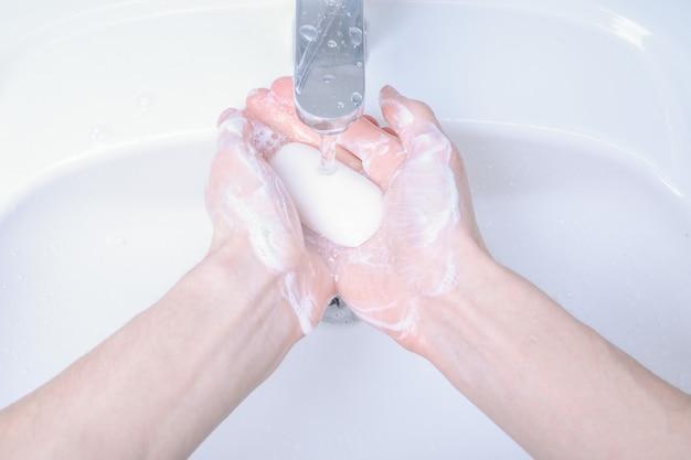 Lavarsi le mani nel lavandino strofinando con soap man per il virus corona, prevenzione covid-19, igiene per fermare la diffusione del coronavirus. distruzione del virus