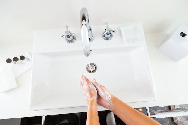 Lavarsi le mani con il sapone sotto l'acqua corrente dall'alto Foto Premium