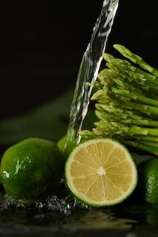 Lavare la calce e gli asparagi con un getto d'acqua, versando l'acqua del rubinetto sulle verdure primo piano