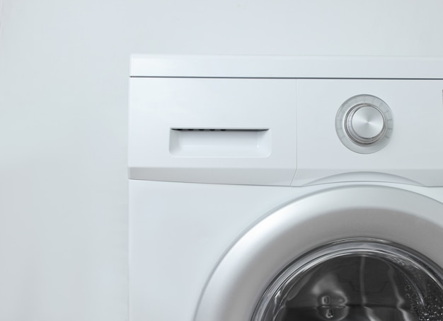 Lavatrice contro una superficie bianca