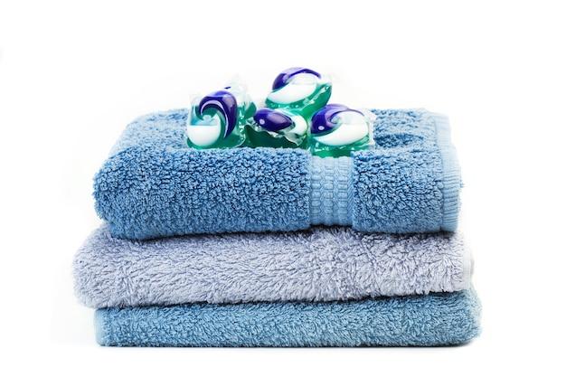 Lavatrice detersivo baccelli su asciugamani blu isolati su sfondo bianco