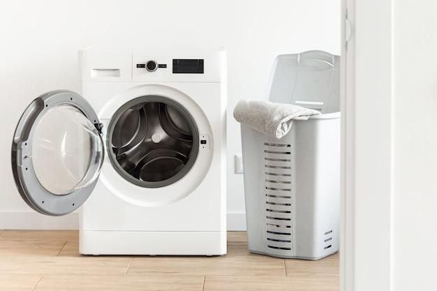 Lavatrice con cesto della biancheria nella lavanderia domestica