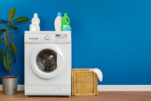 Lavatrice con servizio lavanderia su sfondo blu muro, primi piani.