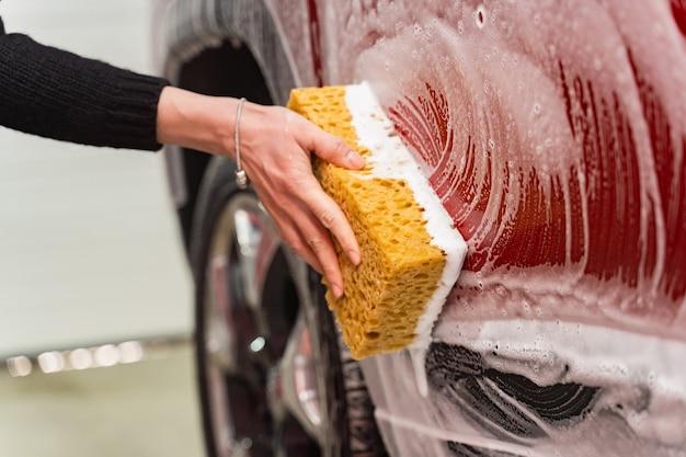 Lavare un'auto rossa con una spugna gialla schiumosa. mano della donna che lava una macchina all'autolavaggio.