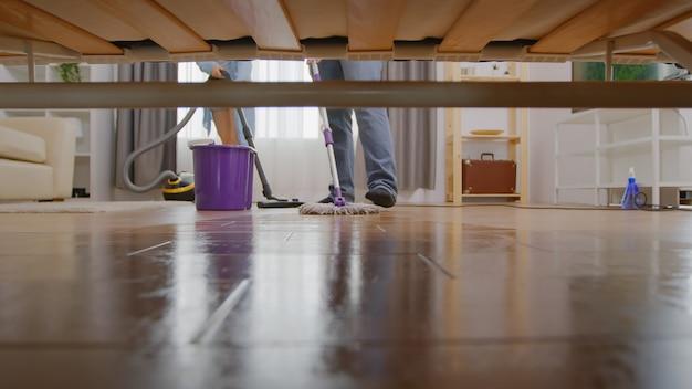 Lavare con uno straccio in casa, vista da sotto il divano