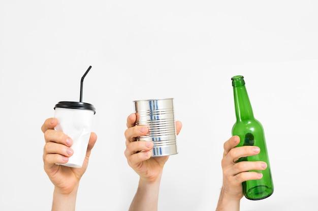 Gestione e smistamento dei rifiuti. plastica, carta, vetro, metallo. mani di persone diverse che tengono immondizia usa e getta