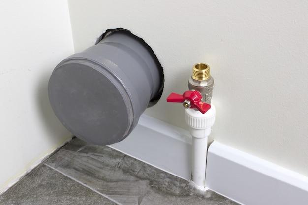 Tubo di scarico e tubo di alimentazione dell'acqua al serbatoio della toilette nell'angolo del bagno.