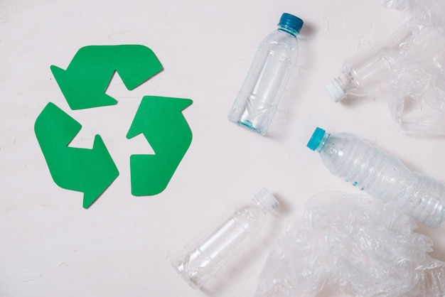 Simbolo ecologico di riciclaggio dei rifiuti con smaltimento dei rifiuti su sfondo tavolo in pietra vista dall'alto