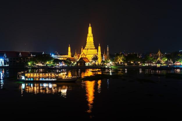 Tempio di wat arun con il fiume chao phraya di notte a bangkok, in thailandia
