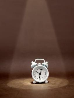 Guarda la sveglia in un fascio di luce su uno sfondo scuro. l'idea di un'azienda, un concetto finanziario e il risparmio di tempo e denaro. formato verticale