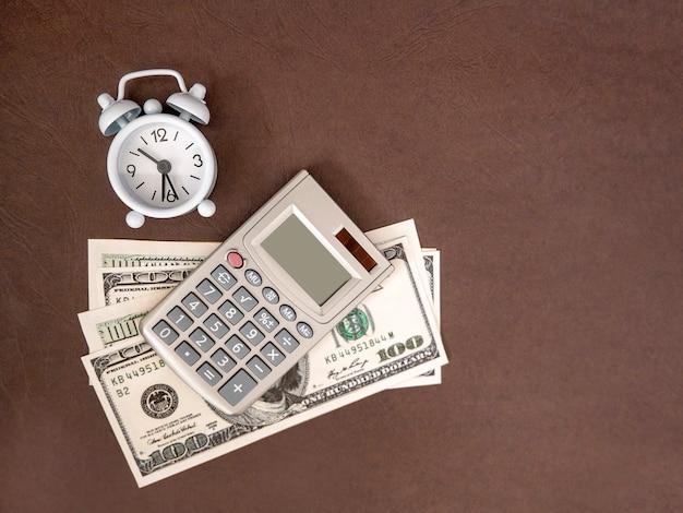 Orologio, calcolatrice, monete e banconote su uno sfondo scuro. l'idea di business, il concetto di finanza e il risparmio di tempo e denaro.
