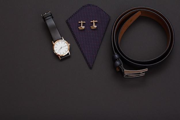Orologio con cinturino in pelle nera, fazzoletto con gemelli e cintura in pelle con fibbia in metallo su sfondo nero. accessori per uomo. vista dall'alto.