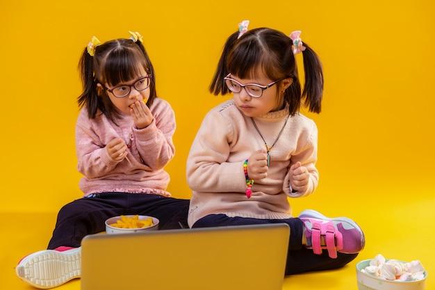 Guardando i cartoni. belle sorelle dai capelli scuri con disturbi mentali seduti contro il laptop e mangiando patatine malsane