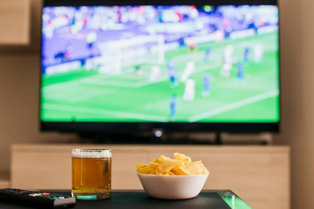 Guardando il concetto di calcio con birra e patatine