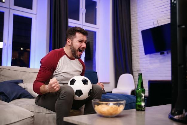 Guardare una partita. giovani allegri che bevono birra e che mangiano gli spuntini mentre guardando la tv