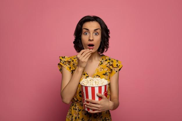 Guardare dei film. giovane donna sorpresa, che sta mangiando popcorn e guardando nella telecamera.