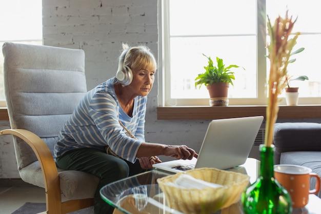 Guardando la lezione online. donna anziana che studia a casa, riceve corsi online, autosviluppo. donna caucasica che utilizza dispositivi moderni per divertirsi, educare, trascorrere del tempo per un nuovo lavoro o hobby.