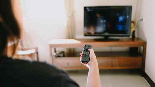 Guardare la smart tv e utilizzare il telecomando tv mano che tiene il telecomando audio della televisione