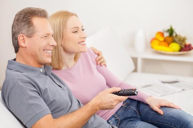 Guardare la tv insieme. vista laterale di una coppia matura allegra seduta insieme e guardando la tv