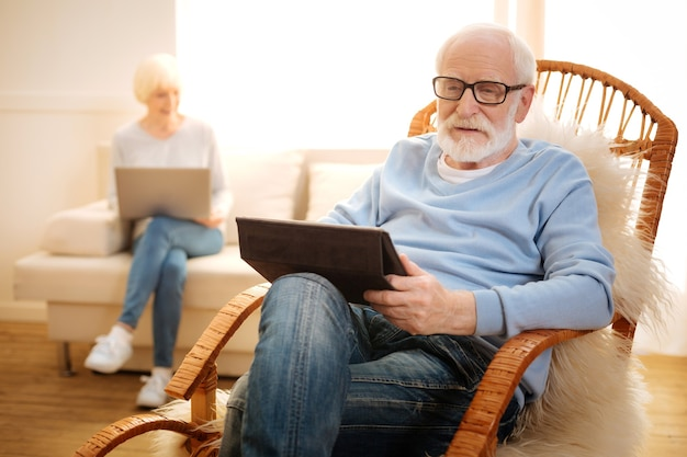 Guardare il video. sagoma di donna felice che si siede e incrocia le gambe durante l'utilizzo di laptop