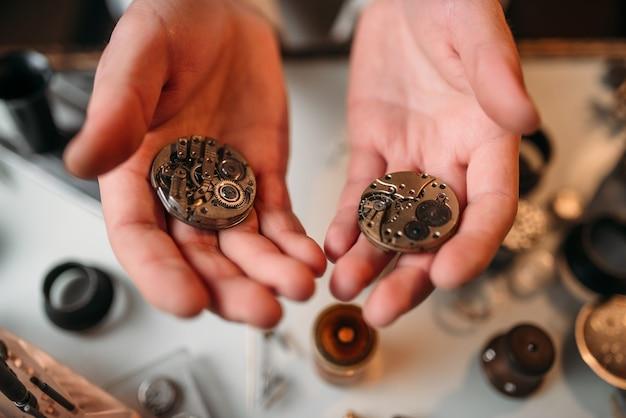 Le mani dell'orologiaio che tengono l'orologio da tasca antico, mostrano il primo piano del meccanismo di orologeria