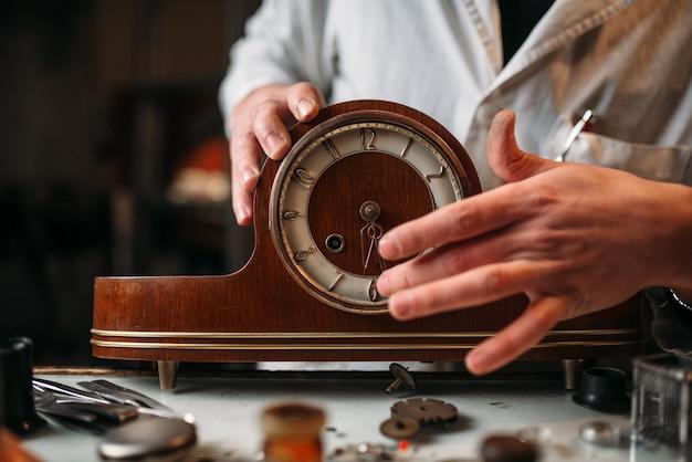L'orologiaio ripristina il vecchio orologio da tavolo in legno