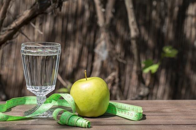 Acqua, mela e centimetro. concetto di fitness. copyspace