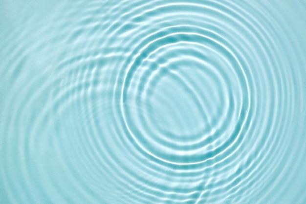 Fondo dell'acqua. struttura dell'acqua blu, superficie dell'acqua blu menta con anelli e increspature. concetto di stazione termale. lay piatto, vista dall'alto, copia spazio.
