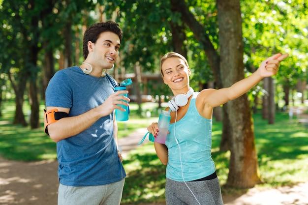 Bilancio idrico. felice giovane donna con in mano una bottiglia d'acqua mentre parla con il suo fidanzato