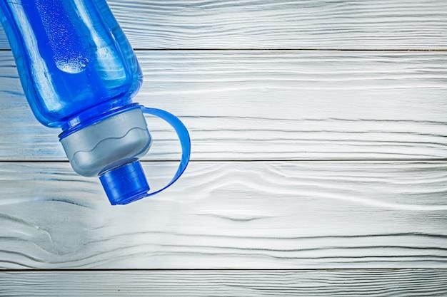 Bottiglia d'acqua per atletica leggera sul concetto di formazione sportiva tavola di legno