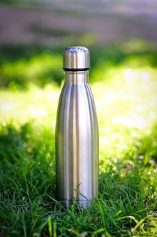 Bottiglia d'acqua su sfondo di erba sfocata con spazio di copia copia spazio foto verticale