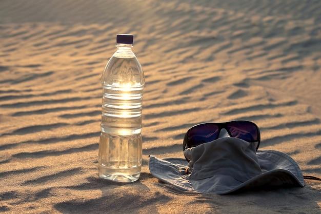 Borraccia, cappello e occhiali da sole sdraiati sulla sabbia nel deserto