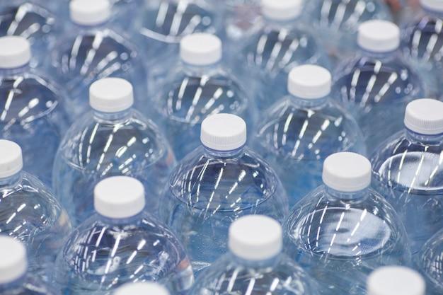 Bottiglie d'acqua nei pacchi del supermercato di acqua potabile pulita in bottiglie di plastica sul bancone del negozio foto di alta qualità