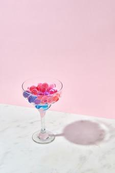 Palline idrogel colorate in acqua in un bicchiere su un tavolo di marmo grigio con ombre contro il muro rosa chiaro, copia dello spazio.
