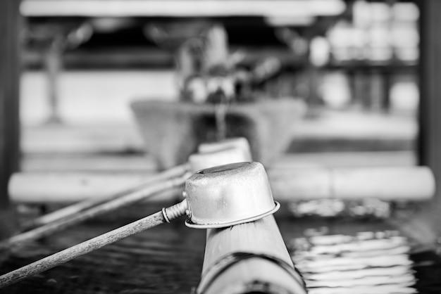 Bicchieri d'acqua in appoggio su un tronco di bambù in una fontana di purificazione in un santuario a kyoto, in giappone.