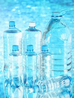 Acqua in bottiglie diverse su sfondo blu
