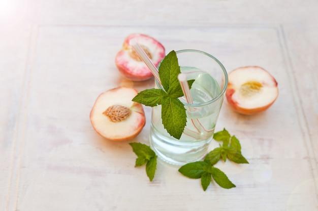 Bevanda d'acqua con pesche rinfrescante tè freddo con menta piperita e pesche su sfondo grigio
