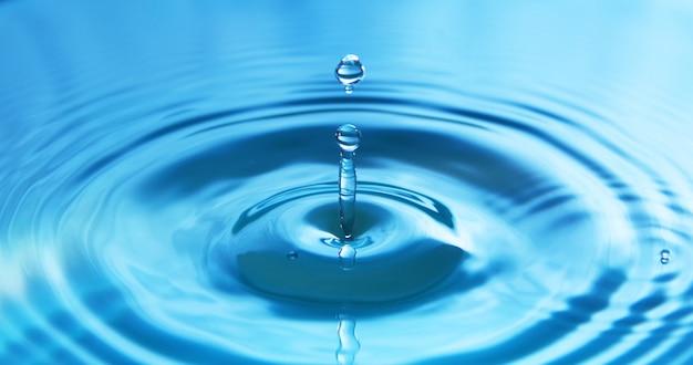 Goccia d'acqua che cade nell'acqua creando un perfetto cerchio concentrico. astratto sfondo blu