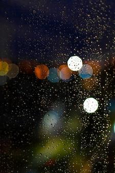 Goccia d'acqua alle finestre e bokeh della città nel tramonto.
