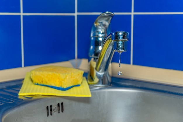 Gocce d'acqua gocciolano che scorre dal rubinetto cromato nel lavandino in cucina su uno sfondo blu. il concetto dell'idea di risparmiare acqua e igiene.