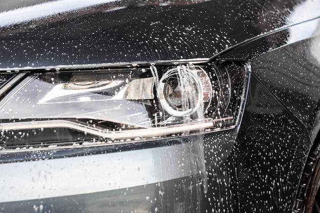 Gocce d'acqua e schiuma sulla luce dell'auto nella stazione di lavaggio del veicolo. concetto di pulizia dell'automobile, inquinamento delle acque sotterranee.