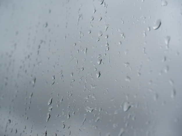 Gocce d'acqua su vetro contro un cielo nuvoloso grigio