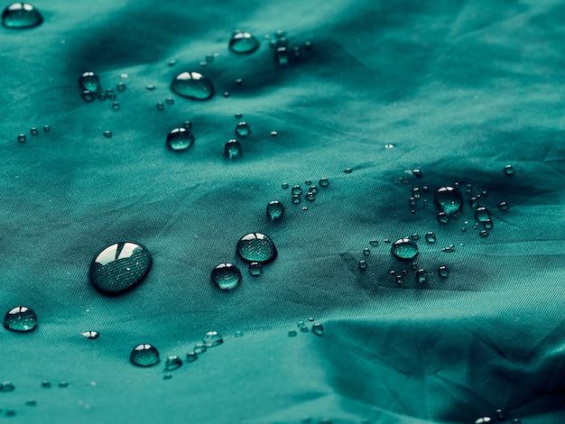 Gocce d'acqua su tessuto a membrana impermeabile. vista in dettaglio della trama del panno impermeabile turchese.