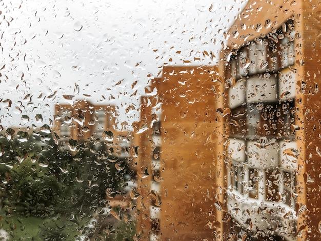 Gocce d'acqua sul vetro della finestra in un giorno di pioggia