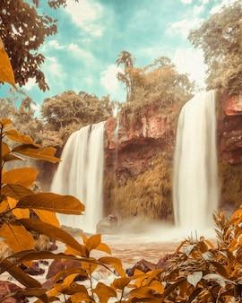 L'acqua cade sotto il cielo blu in cataratas fa iguacu - il brasile