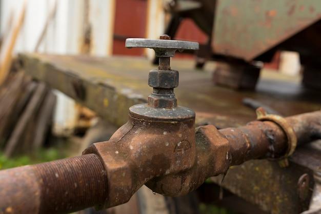Rubinetto dell'acqua e tubi dell'acqua arrugginiti, fonti d'acqua per i campi degli agricoltori foto di alta qualità