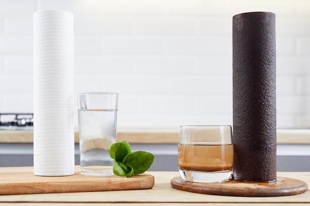 Cartuccia del filtro dell'acqua usata e un bicchiere di colorazione marrone acqua sporca e nuovo filtro puro con un bicchiere di acqua pulita dai sistemi di osmosi dell'acqua domestica alla cucina moderna.
