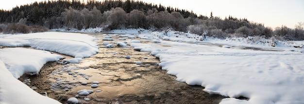 Acqua che scorre tra ghiaccio e neve in un fiume in inverno